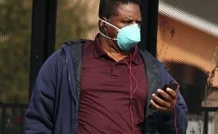 Un homme portant un masque attend le bus à San Francisco, le 15 novembre 2018.
