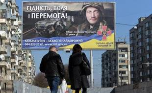 Des personnes marchent devant un panneau appelant les ukrainiens à rejoindre l'armée à Lviv le 17 mars 2015