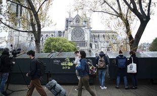 Passants devant Notre-Dame de Paris au lendemain de son incendie du 15 avril 2019