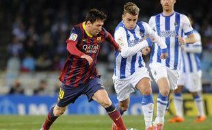 L'attaquant français de la Real Sociedad Antoine Griezmann contre Lionel Messi et le FCBarcelone, le 22 février 2014, à San Sebastien.