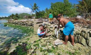 Photo non datée d'habitants de l'île Christmas (aussi appelée Kiritimati) de la République des Kiribati édifiant un mur de pierre pour se protéger de la montée des eaux