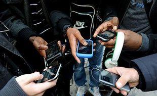 Des jeunes utilisent leur téléphone portable