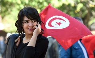 Une jeune femme tunisienne agite le drapeau national à Tunis.