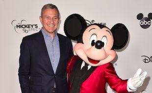 Bob Iger, PDG de la Walt Disney Company, au côté d'un comédien incarnant Mickey Mouse, lors d'une soirée de gala, en octobre 2018.