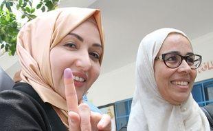 Une Tunisienne montre son doigt bleuté, coloré par l'encre, une preuve de son vote dimanche 6 mai.