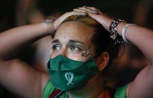 Un militant des droits à l'avortement regarde la diffusion en direct des législateurs en session, en dehors du Congrès à Buenos Aires, en Argentine, le mercredi 30 décembre 2020.