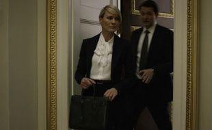 Claire Undewood porte un sac de jour et une blouse Hedi Slimane pour Saint Laurent.