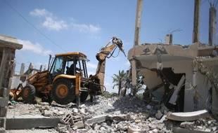 Des Palestiniens font des travaux pour enlever les ruines d'immeubles détruits lors de la guerre à Gaza en 2014, dans le village de Khuzaa, dans la Bande de Gaza, le 1er juin 2015