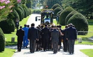 Employees of the Chateau Mouton Rothschild (in blue) and relatives walk next to the coffin carrying the body of baroness Philippine de Rothschild, pulled by a vineyard tractor, during her funeral ceremony on September 1, 2014 in Pauillac, western France. AFP PHOTO / JEAN-PIERRE MULLER