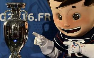 Super Victor, la mascotte de l'Euro 2016, pose à côté du trophée, le 12 mai 2015, à Paris.
