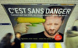 Des gens passent devant l'affiche d'une campagne contre les organismes génétiquement modifiés (OGM), le 15 février 2011, dans une station du métro parisien
