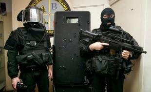 Des policiers de la BRI posent à côté d'un bouclier le 17 novembre 2015 à Paris sur lequel on voit les impacts de balles des terroristes, lors de l'intervention au Bataclan