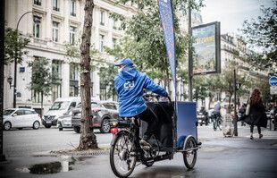 Un distributeur du journal 20 Minutes sur un triporteur dans les rues de Paris, le 12 octobre 2020.