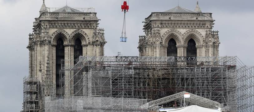 A box hangs from a crane at Notre Dame cathedral, Monday, June 8, 2020 in Paris. Workers suspended from ropes will be lowered into the charred remains of scaffolding that melted atop Notre Dame when the cathedral went up in flames and begin the delicate job of dismantling the 200 tons of metal.