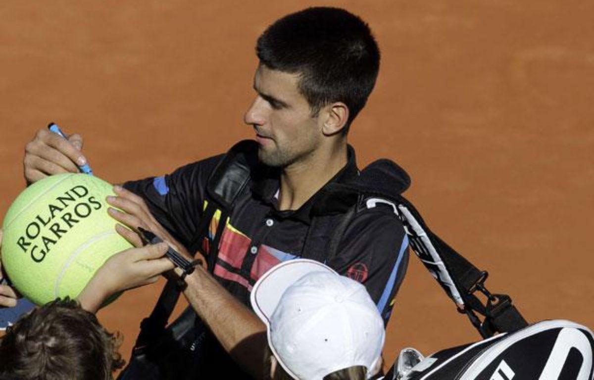 Le Serbe Novak Djokovic signe des autographes à la fin de son match contre Victor Hanescu, le 25 mai 2011 à Roland-Garros. – REUTERS
