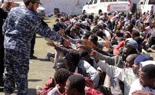 Des migrants de l'Afrique sous-saharienne reçoivent à boire le 17 mai 2015 dans un centre de détention de Tripoli, en Libye, après avoir été arrêtés alors qu'ils tentaient de traverser la Méditerranée à bord de bateaux de passeurs illégaux