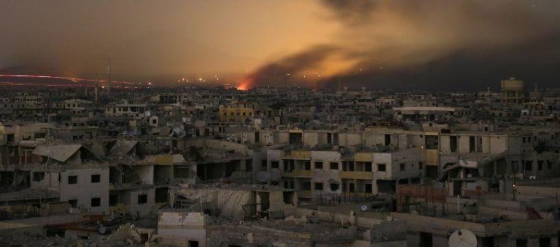De la lumière et de la fumée sur le quartier de la Ghouta orientale en Syrie, le 11 mars 2018.