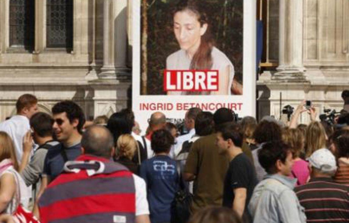 """La foule massée devant le portrait géant d'Ingrid Betancourt avec le mot """"LIBRE"""" ajouté par des employés municipaux, sur la facade de l'Hôtel de ville le 3 juillet 2008. – REUTERS/Benoît Tessier"""