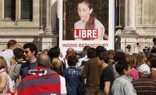"""La foule massée devant le portrait géant d'Ingrid Betancourt avec le mot """"LIBRE"""" ajouté par des employés municipaux, sur la facade de l'Hôtel de ville le 3 juillet 2008."""