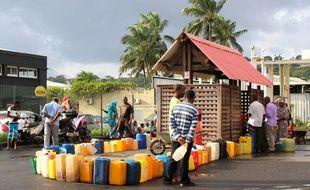 Des habitants de l'île remplissent des jerrycans d'essence, alors que les routes sont bloquées à Mayotte, le 7 mars 2018.