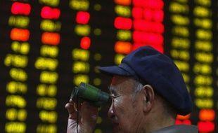 Un homme suit les cours de la Bourse à la jumelle, dans la province du Hubei, en Chine, le 28 mars 2008.