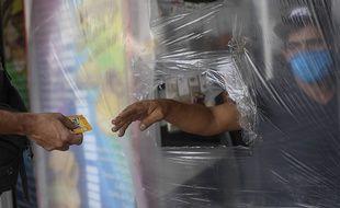 Un caissier derrière un rideau en plastique à Caracas, au Venezuela, le 29 mars 2020.