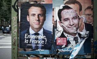 Des affiches d'Emmanuel Macron et de Benoît Hamon.