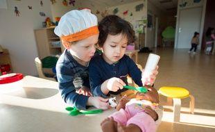 Deux enfants -deux garçons- donnent à manger à une poupée, à Gien. (illustration)