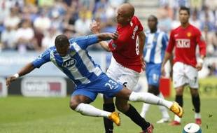 Manchester United's Wes Brown (R) challenges Wigan Athletic's Marcus Bent (L) for the ball during their English Premier League soccer match in Wigan, northern England, May 11, 2008. REUTERS/Phil Noble (BRITAIN