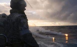 Un homme observe les signaux d'un avion de la New Zealand Air Force lors de recherches de débris du vol MH370 dans le Sud de l'Océan Indien le 13 avril 2014