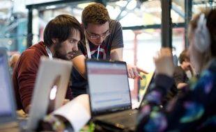 """Des participants travaillent sur leurs ordinateurs lors du marathon de la programmation """"hackathon"""", à Londres le 25 avril 2015"""