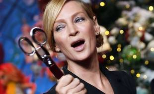 U.S. actress Uma Thurman poses with the scissors used to cut the red ribbon during the unveiling of a Christmas-themed shop window displayed at Le Printemps department store in Paris, Thursday Nov. 3, 2016. (AP Photo/Francois Mori)/ZFM114/16308639352149/1611031849