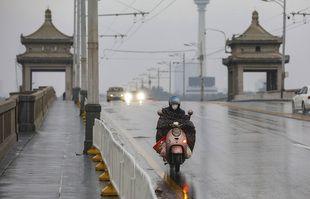 Un motocycliste traverse un pont à Wuhan, dans la province du Hubei, dans le centre de la Chine, le 25 janvier 2020.