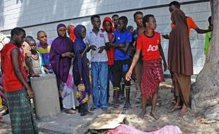 Des somaliens devant le corps d'une victime de l'explosion d'une voiture piégée devant un restaurant très fréquenté de Mogadiscio, le 21 avril 2015