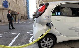 Un véhicule électrique à une borne de recharge.