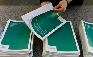 Un bénévole feuillette le rapport de la commission d'enquête allemande sur la collection Gurlitt, avant une conférence de presse à Berlin, le 14 janvier 2016.