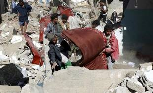 Des Yéménites récupèrent des biens des débris des maisons détruites par les raids aériens conduits par l'Arabie saoudite, le 1er mai 2015 à Sanaa, la capitale du pays