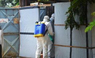 Des membres de la Croix Rouge préparent un corps à être enterré, dans la zone d'un hôpital de Conakry où les malades d'Ebola sont soignés, le 28 juin 2014