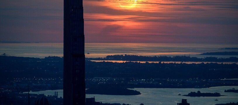 L'éclipse de soleil partielle est visible derrière la skyline de Manhattan, à New York, le 10 juin 2021.