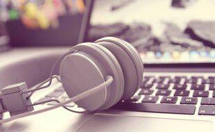 Illustration d'un casque audio devant un ordinateur.