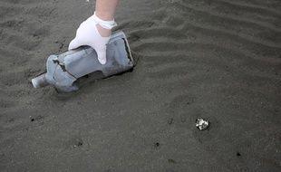 Un volontaire ramasse une bouteille en plastique sur une plage en Grèce le 3 février.