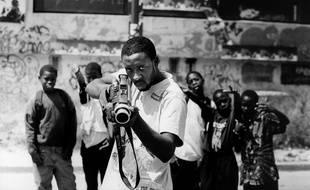 De 2004 à 2006, JR réalise Portrait d'une génération, des portraits de jeunes de banlieue qu'il expose, en très grand format, sur les murs de la Cité des Bosquets de Montfermeil. Ici, le portrait de Ladj Ly, reproduit dans l'ouvrage « 28 Millimètres, Portrait d'une génération ».