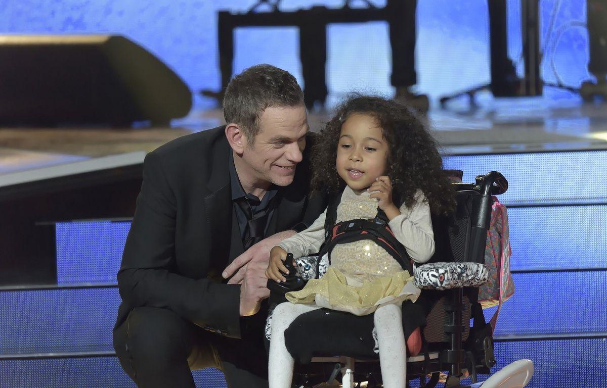 Le chanteur Garou aux côtés d'une petite fille atteinte de myopathie, lors de la soirée du Téléthon 2014.  – SADAKA EDMOND/SIPA