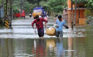 Des hommes transportent de la nourriture et de l'eau pour les distribuer aux personnes bloquées par les inondations à Pandanad, dans le district d'Alappuzha, dans l'État du Kerala, dans le sud de l'Inde, le 21 août 2018.