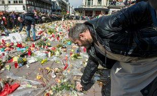Un homme dépose des fleurs devant un mémorial improvisé place de la Bourse à Bruxelles lors de la marche pacifiste contre le terrorisme le 17 avril 2016