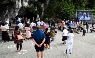 Des pèlerins devant la grotte de Massabielle, à Lourdes, le 30 mai 2020.