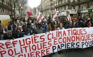 Des manifestants défilent à Paris pour soutenir migrants et travailleurs sans papiers, à l'appel de plusieurs syndicats et associations, le 19 décembre 2015