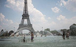 A Paris, le 26 juillet, des Parisiens se rafraîchissent dans les fontaines du Trocadero.