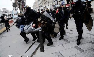 Paris, le 29 décembre 2018. Des policiers embarquent un manifestant des «gilets jaunes» lors de la manifestation sur les Champs-Elysées.