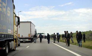 Illustration de migrants tentant de s'introduire dans les camions en direction de la Grande-Bretagne.